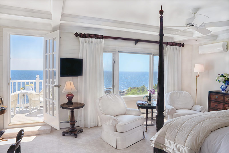 Bedroom with white sitting chair, tv and ocean views