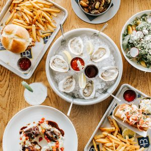 the boathouse waterfront hotel table full of food fried chicken sandwich fried brussels srouts farm to fork salad half dozen oysters lobster roll french fries cole slaw
